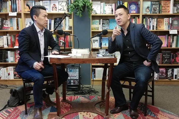 Viet Thanh Nguyen speaking, seated at a table with Jack Wang.